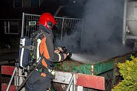 Brandweer blust brand in bouwcontainer